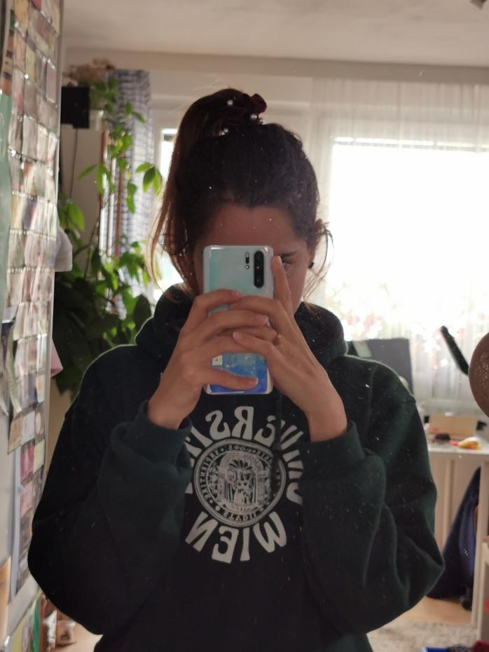 Frau fotografiert sich im Spiegel. Gesicht ist mit dem Handy verdeckt, am Pulli ist das Logo der Universität Wien.